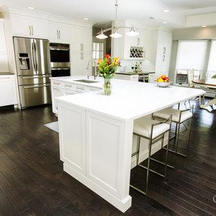 Klassisk inredning av ett stort kök, med en undermonterad diskho, luckor med infälld panel, vita skåp, bänkskiva i kvarts, grönt stänkskydd, stänkskydd i glaskakel, rostfria vitvaror, mörkt trägolv och en köksö