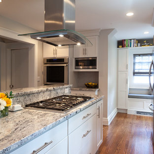 Inspiration for a mid-sized midcentury l-shaped eat-in kitchen in New York with a single-bowl sink, recessed-panel cabinets, white cabinets, granite benchtops, grey splashback, ceramic splashback, stainless steel appliances, medium hardwood floors and with island.