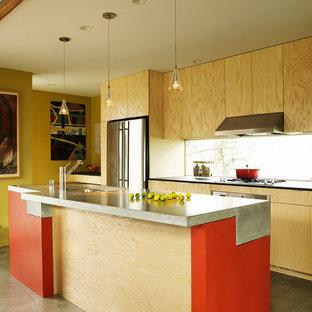 Idéer för ett industriellt parallellkök, med en enkel diskho, släta luckor, skåp i ljust trä, bänkskiva i betong, rostfria vitvaror, betonggolv och en köksö