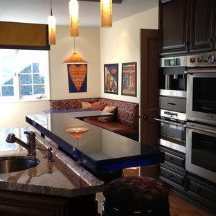 オレンジカウンティの広いエクレクティックスタイルのおしゃれなキッチン (アンダーカウンターシンク、レイズドパネル扉のキャビネット、濃色木目調キャビネット、御影石カウンター、ガラスタイルのキッチンパネル、シルバーの調理設備、無垢フローリング) の写真