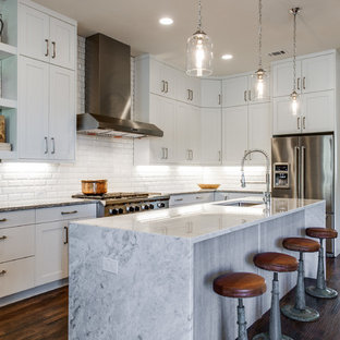 Photo of a country l-shaped kitchen in Dallas with an undermount sink, shaker cabinets, white cabinets, white splashback, stainless steel appliances, dark hardwood floors and with island.