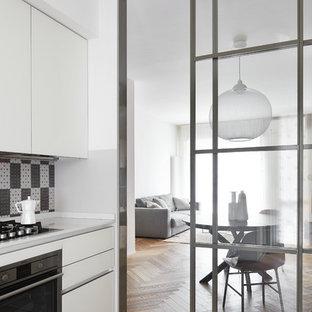 Ispirazione per una cucina contemporanea con ante lisce, ante bianche, paraspruzzi multicolore, elettrodomestici in acciaio inossidabile e pavimento in legno massello medio