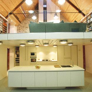 チャネル諸島のコンテンポラリースタイルのおしゃれなキッチン (ドロップインシンク、フラットパネル扉のキャビネット、白いキャビネット、白いキッチンパネル) の写真