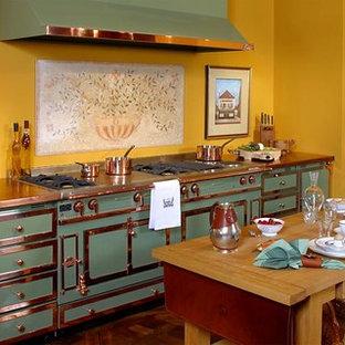 На фото: отдельные кухни в классическом стиле с фасадами с утопленной филенкой, зелеными фасадами, столешницей из меди, цветной техникой, темным паркетным полом, островом и коричневым полом