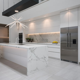 Contemporary kitchen designs - Kitchen - contemporary galley white floor kitchen idea in Auckland with an undermount sink, flat-panel cabinets, white cabinets, white backsplash, stone slab backsplash, stainless steel appliances, an island and white countertops