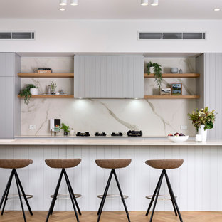 Photo of a contemporary galley kitchen in Brisbane with flat-panel cabinets, grey cabinets, white splashback, stone slab splashback, medium hardwood floors, with island, brown floor and white benchtop.
