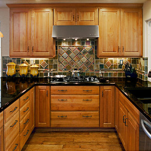 Example of a small classic u-shaped medium tone wood floor eat-in kitchen design in Orange County with a double-bowl sink, raised-panel cabinets, light wood cabinets, granite countertops, multicolored backsplash, stone tile backsplash, stainless steel appliances and a peninsula