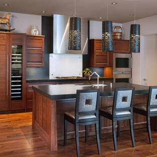 サンディエゴのアジアンスタイルのおしゃれなキッチン (アンダーカウンターシンク、濃色木目調キャビネット、白いキッチンパネル、ガラス板のキッチンパネル、シルバーの調理設備) の写真