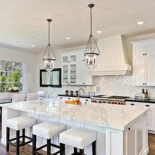サンディエゴの大きい地中海スタイルのおしゃれなキッチン (エプロンフロントシンク、シェーカースタイル扉のキャビネット、白いキャビネット、白いキッチンパネル、シルバーの調理設備、大理石カウンター、無垢フローリング) の写真