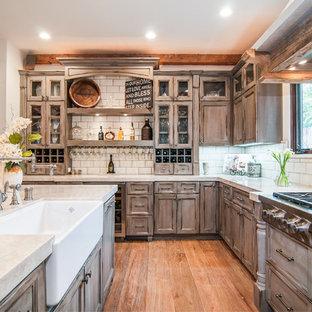 サンディエゴの地中海スタイルのおしゃれなキッチン (エプロンフロントシンク、シェーカースタイル扉のキャビネット、中間色木目調キャビネット、白いキッチンパネル、サブウェイタイルのキッチンパネル、シルバーの調理設備の、無垢フローリング) の写真