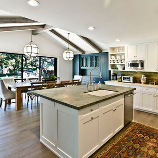 This is an example of a large contemporary u-shaped eat-in kitchen in Los Angeles with an integrated sink, shaker cabinets, white cabinets, onyx benchtops, green splashback, stainless steel appliances, medium hardwood floors and with island.
