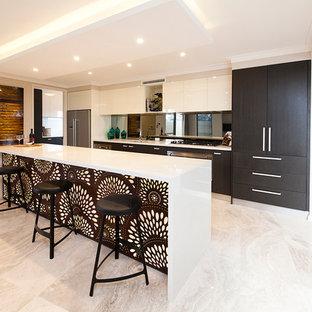 Ejemplo de cocina lineal, contemporánea, abierta, con armarios con paneles lisos, puertas de armario de madera en tonos medios, salpicadero con efecto espejo, electrodomésticos de acero inoxidable y suelo beige