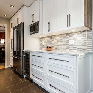 Inspiration for a small scandinavian galley separate kitchen in Montreal with an undermount sink, shaker cabinets, white cabinets, grey splashback, glass tile splashback, stainless steel appliances, ceramic floors and no island.
