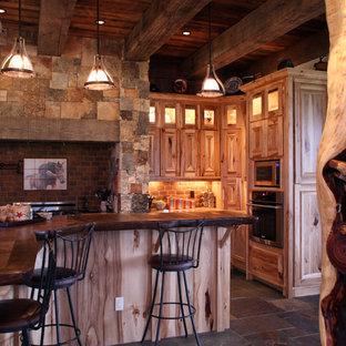 Offene, Große Rustikale Küche in L-Form mit Schrankfronten mit vertiefter Füllung, hellen Holzschränken, Arbeitsplatte aus Holz, Küchenrückwand in Rot, Küchengeräten aus Edelstahl, Schieferboden, Rückwand aus Stein und Kücheninsel in Albuquerque