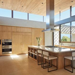 Свежая идея для дизайна: большая угловая кухня в стиле модернизм с плоскими фасадами, светлыми деревянными фасадами, столешницей из бетона, серым фартуком, фартуком из цементной плитки, техникой из нержавеющей стали, полом из известняка, островом, бежевым полом, серой столешницей и монолитной раковиной - отличное фото интерьера