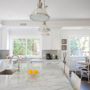 Large transitional open concept kitchen ideas - Inspiration for a large transitional l-shaped dark wood floor open concept kitchen remodel in Los Angeles with shaker cabinets, white cabinets, an undermount sink, marble countertops, gray backsplash, glass sheet backsplash, stainless steel appliances and an island