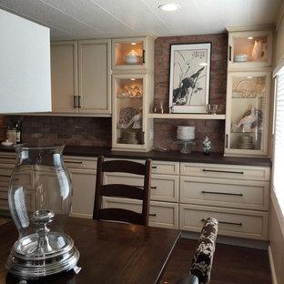 Bild på ett mellanstort linjärt kök med öppen planlösning, med en enkel diskho, luckor med infälld panel, skåp i slitet trä, bänkskiva i kvartsit, rött stänkskydd, stänkskydd i tunnelbanekakel, svarta vitvaror, mörkt trägolv och en köksö