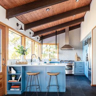 Idéer för att renovera ett mellanstort, avskilt lantligt vit vitt u-kök, med en rustik diskho, skåp i shakerstil, blå skåp, bänkskiva i kvarts, vitt stänkskydd, stänkskydd i tunnelbanekakel, rostfria vitvaror, klinkergolv i porslin, en halv köksö och grått golv