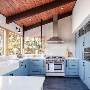 Inredning av ett lantligt mellanstort vit vitt u-kök, med en rustik diskho, skåp i shakerstil, blå skåp, rostfria vitvaror, grått golv, vitt stänkskydd, en halv köksö, bänkskiva i kvarts, stänkskydd i tunnelbanekakel och klinkergolv i porslin