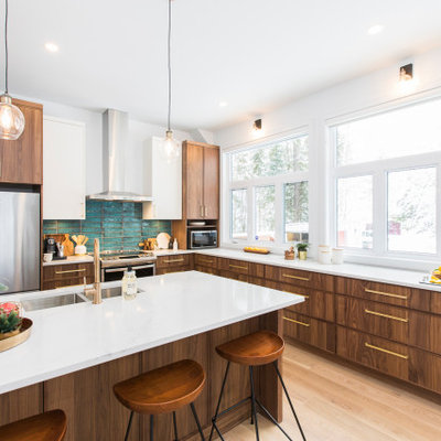 Example of a large 1960s l-shaped light wood floor and beige floor open concept kitchen design in Ottawa with a double-bowl sink, medium tone wood cabinets, quartz countertops, blue backsplash, ceramic backsplash, stainless steel appliances, white countertops, flat-panel cabinets and a peninsula