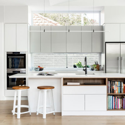 Beach style light wood floor kitchen photo in Sydney with an undermount sink, flat-panel cabinets, gray cabinets, window backsplash, stainless steel appliances, an island and white countertops