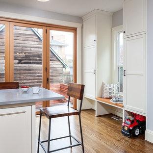 ポートランドの中サイズのカントリー風おしゃれなキッチン (エプロンフロントシンク、シェーカースタイル扉のキャビネット、白いキャビネット、人工大理石カウンター、白いキッチンパネル、サブウェイタイルのキッチンパネル、シルバーの調理設備の、濃色無垢フローリング、茶色い床) の写真