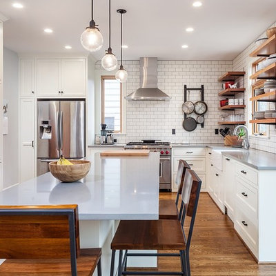 Inspiration for a mid-sized country l-shaped medium tone wood floor and brown floor eat-in kitchen remodel in Portland with a farmhouse sink, white cabinets, solid surface countertops, white backsplash, subway tile backsplash, stainless steel appliances, an island and open cabinets