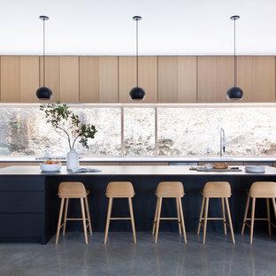 Modern inredning av ett mycket stort vit vitt kök, med en köksö, släta luckor, skåp i ljust trä, fönster som stänkskydd, rostfria vitvaror och grått golv