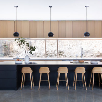 Eat-in kitchen - huge contemporary u-shaped gray floor eat-in kitchen idea in Austin with an island, flat-panel cabinets, light wood cabinets, window backsplash, stainless steel appliances and white countertops