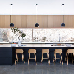 Inspiration for a modern kitchen in Austin with flat-panel cabinets, light wood cabinets, window splashback, stainless steel appliances, concrete flooring, an island, grey floors and white worktops.