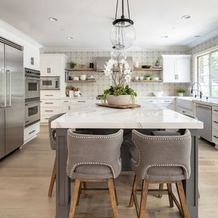 Transitional kitchen designs - Kitchen - transitional light wood floor kitchen idea in Orange County with a farmhouse sink, quartz countertops, cement tile backsplash, stainless steel appliances, an island and white countertops