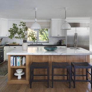 Foto på ett mellanstort vintage vit kök, med luckor med profilerade fronter, vita skåp, marmorbänkskiva, vitt stänkskydd, en köksö, brunt golv, en undermonterad diskho, stänkskydd i cementkakel, rostfria vitvaror och mellanmörkt trägolv