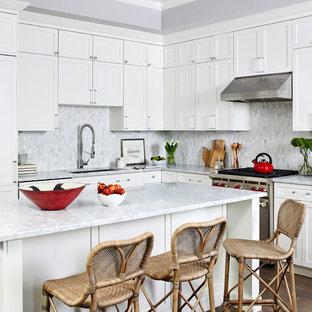Klassische Wohnküche in L-Form mit Unterbauwaschbecken, Schrankfronten mit vertiefter Füllung, weißen Schränken, Küchenrückwand in Grau, Rückwand aus Mosaikfliesen, Küchengeräten aus Edelstahl, braunem Holzboden, Kücheninsel, braunem Boden und grauer Arbeitsplatte in Los Angeles