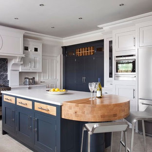 Design ideas for a large traditional u-shaped kitchen/diner in Belfast with a submerged sink, beaded cabinets, quartz worktops, grey splashback, stone slab splashback, stainless steel appliances, ceramic flooring, an island and white cabinets.
