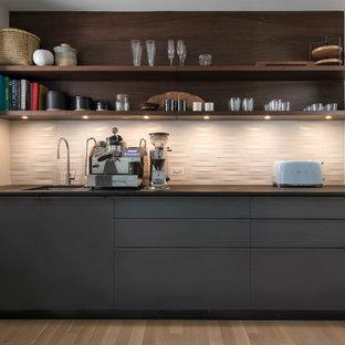 Diseño de cocina lineal, vintage, sin isla, con despensa, fregadero bajoencimera, armarios con paneles lisos, puertas de armario grises, salpicadero blanco, suelo de madera clara, suelo beige y encimeras negras
