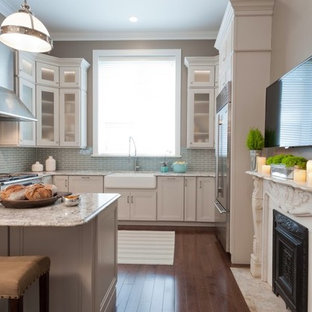 Mid-sized transitional l-shaped dark wood floor eat-in kitchen photo in St Louis with a farmhouse sink, quartz countertops, blue backsplash, glass tile backsplash, stainless steel appliances, recessed-panel cabinets, white cabinets and a peninsula