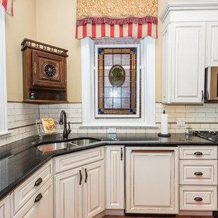 セントルイスの大きいヴィクトリアン調のおしゃれなキッチン (ダブルシンク、レイズドパネル扉のキャビネット、白いキャビネット、クオーツストーンカウンター、白いキッチンパネル、サブウェイタイルのキッチンパネル、シルバーの調理設備の、無垢フローリング) の写真