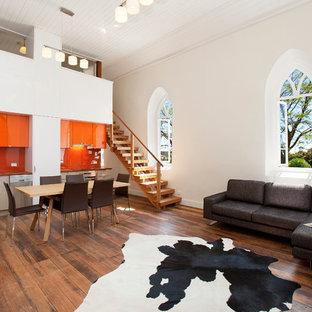 Industriell inredning av ett linjärt kök med öppen planlösning, med en undermonterad diskho, släta luckor, orange skåp, orange stänkskydd, glaspanel som stänkskydd och rostfria vitvaror