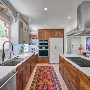 This is an example of a mid-sized contemporary l-shaped eat-in kitchen in Sacramento with an undermount sink, shaker cabinets, medium wood cabinets, quartz benchtops, white splashback, porcelain splashback, stainless steel appliances, light hardwood floors, a peninsula, multi-coloured floor and white benchtop.