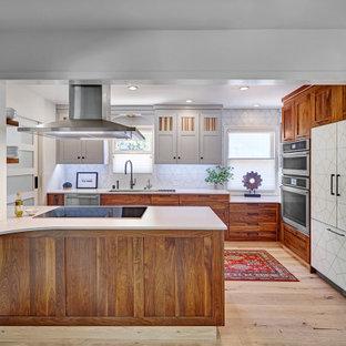 サクラメントの中くらいのエクレクティックスタイルのおしゃれなキッチン (アンダーカウンターシンク、シェーカースタイル扉のキャビネット、中間色木目調キャビネット、クオーツストーンカウンター、白いキッチンパネル、磁器タイルのキッチンパネル、シルバーの調理設備、淡色無垢フローリング、マルチカラーの床、白いキッチンカウンター) の写真
