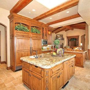 Inspiration för ett stort medelhavsstil l-kök, med en undermonterad diskho, luckor med upphöjd panel, skåp i mellenmörkt trä, granitbänkskiva, beige stänkskydd, stänkskydd i stenkakel, integrerade vitvaror, travertin golv, en köksö och beiget golv