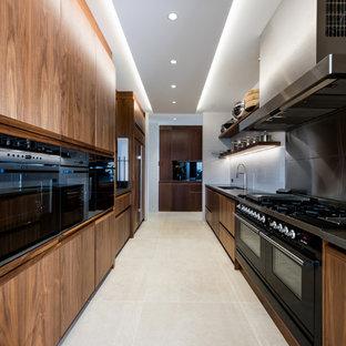 Réalisation d'une très grand arrière-cuisine parallèle ethnique avec un évier encastré, des portes de placard en bois brun, un plan de travail en granite, une crédence multicolore et une crédence en carreau de miroir.