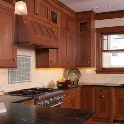 Example of an arts and crafts u-shaped eat-in kitchen design in Chicago with shaker cabinets, medium tone wood cabinets, soapstone countertops, beige backsplash, subway tile backsplash, stainless steel appliances and an undermount sink