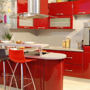 This is an example of a small modern u-shaped open plan kitchen in Orange County with a drop-in sink, flat-panel cabinets, red cabinets, solid surface benchtops, grey splashback, light hardwood floors, a peninsula and beige floor.