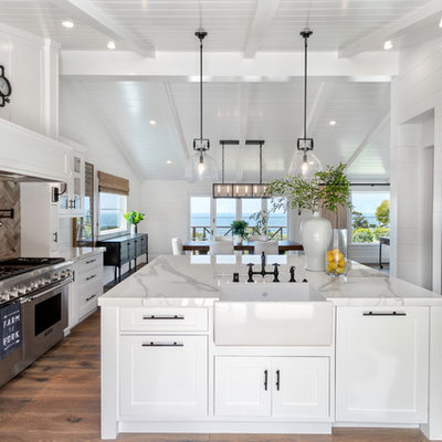 Mid-sized cottage u-shaped medium tone wood floor and brown floor eat-in kitchen photo in Orange County with a farmhouse sink, shaker cabinets, white cabinets, stainless steel appliances, an island, white countertops, marble countertops, white backsplash and wood backsplash