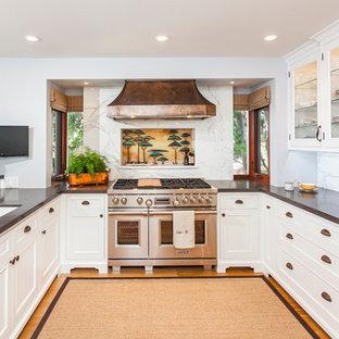 Inspiration pour une cuisine traditionnelle en U avec un évier encastré, des portes de placard blanches, une crédence blanche, un électroménager en acier inoxydable, aucun îlot et un placard à porte vitrée.
