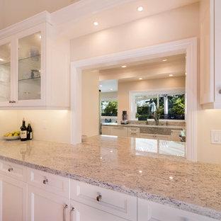 Foto på ett stort vintage kök, med en undermonterad diskho, släta luckor, vita skåp, granitbänkskiva, vitt stänkskydd, stänkskydd i porslinskakel, rostfria vitvaror, bambugolv och en halv köksö