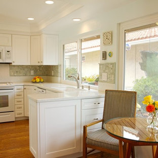 Mid-sized traditional eat-in kitchen designs - Mid-sized elegant u-shaped light wood floor eat-in kitchen photo in Orange County with a drop-in sink, recessed-panel cabinets, white cabinets, quartz countertops, green backsplash, mosaic tile backsplash, white appliances and a peninsula