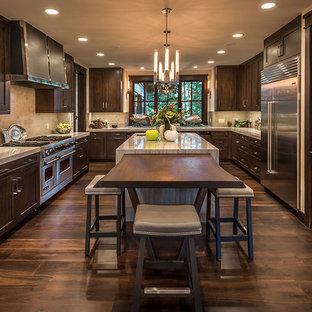 Imagen de cocina rústica con armarios estilo shaker, puertas de armario de madera en tonos medios, salpicadero beige, electrodomésticos de acero inoxidable, suelo de madera oscura, suelo marrón y dos o más islas