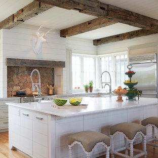 Ejemplo de cocina en L, marinera, con fregadero sobremueble, armarios con rebordes decorativos, puertas de armario blancas, electrodomésticos de acero inoxidable, suelo de madera en tonos medios, una isla y suelo marrón